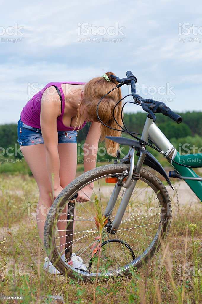 attractive girl inflating bike wheel stock photo