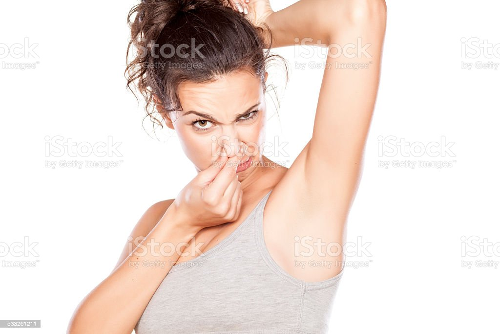 Attractive girl is disgusted by her sweaty armpits stock photo