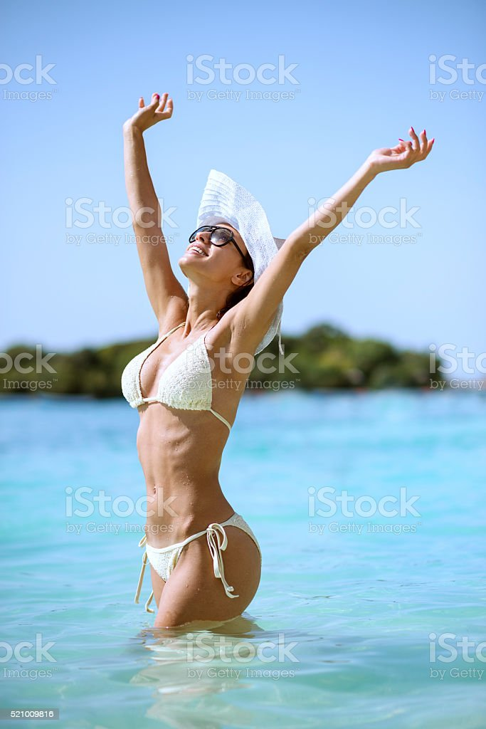 Attractive Girl Sunbathing in Sea with Arms Raised to Sky stock photo