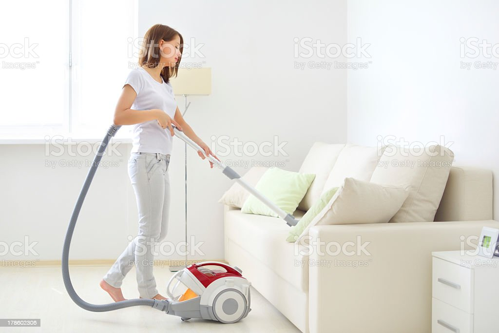 Attractive girl vacuuming a white couch stock photo