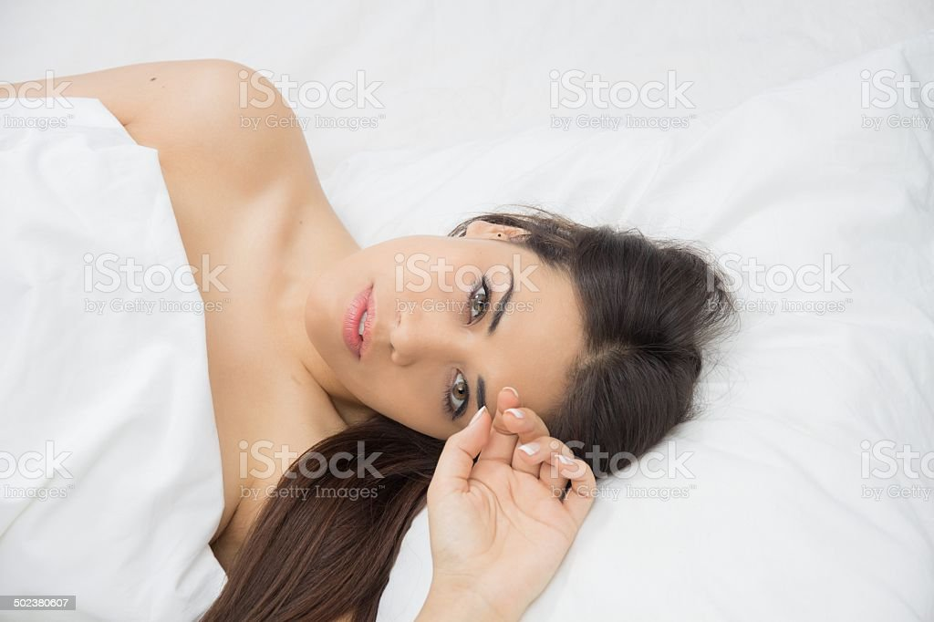 Attractive girl wakes up in bed stock photo