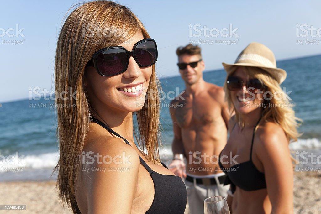 Belle fille avec des amis à la plage. photo libre de droits