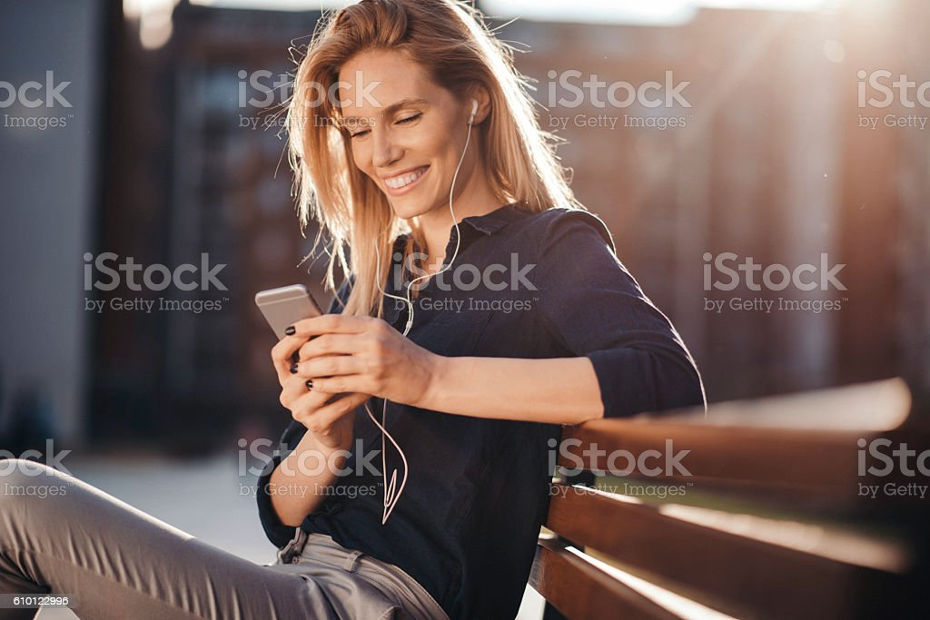 Attractive girl with headphones embracing the sunny day stock photo