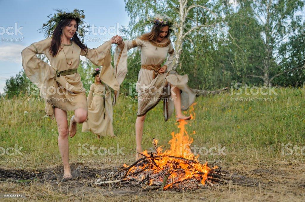Attractive girls jump through fire stock photo