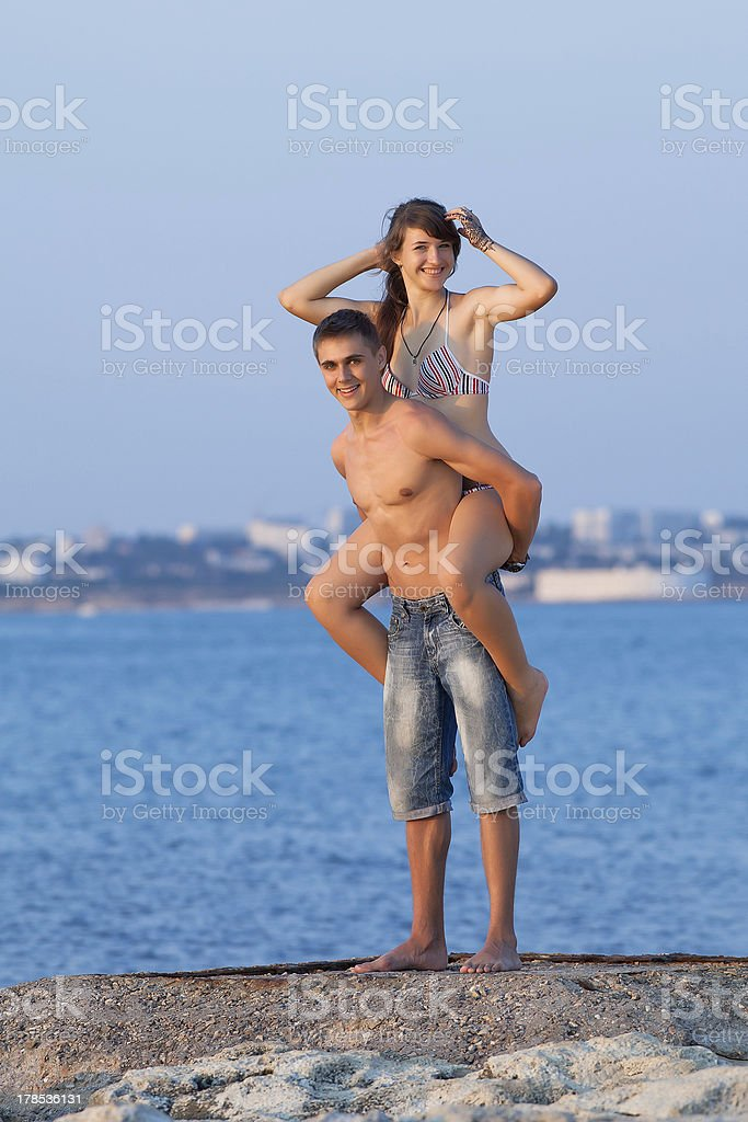 Attractive guy and girl playing at the sea royalty-free stock photo