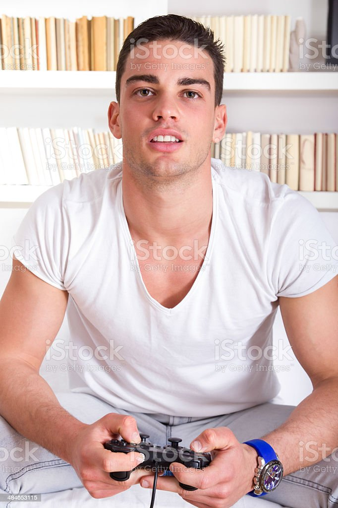 attractive guy concentrating while playing video games royalty-free stock photo