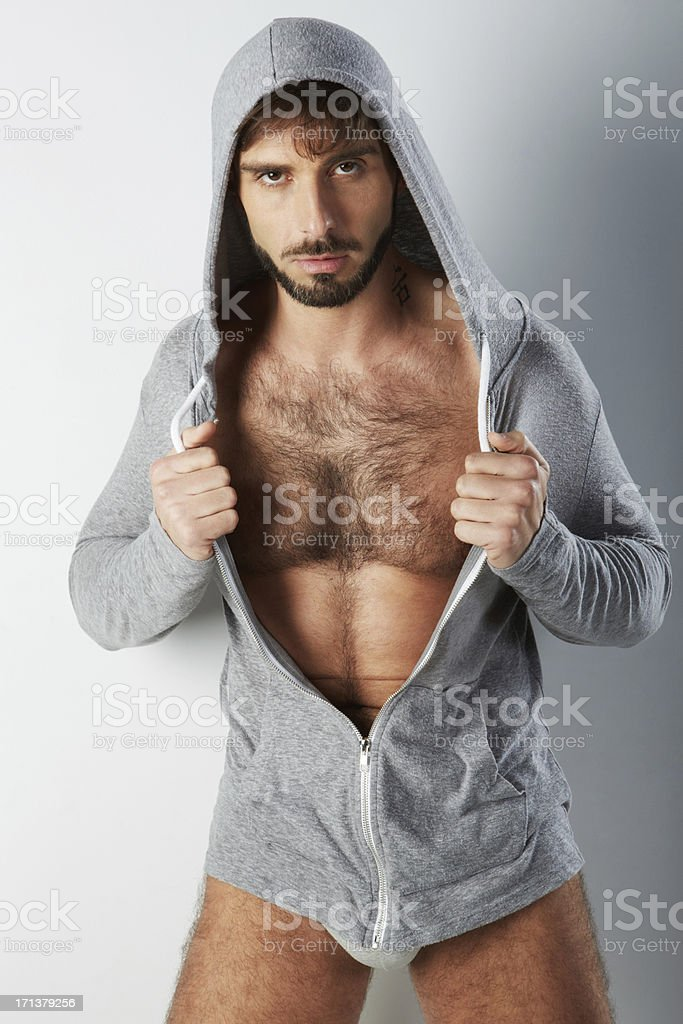 Attractive hairy man in underwear with hooded sweater holding stock photo