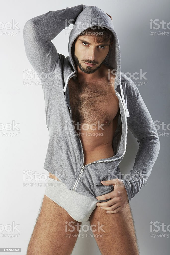 Attractive hairy man in underwear with hooded sweater stock photo