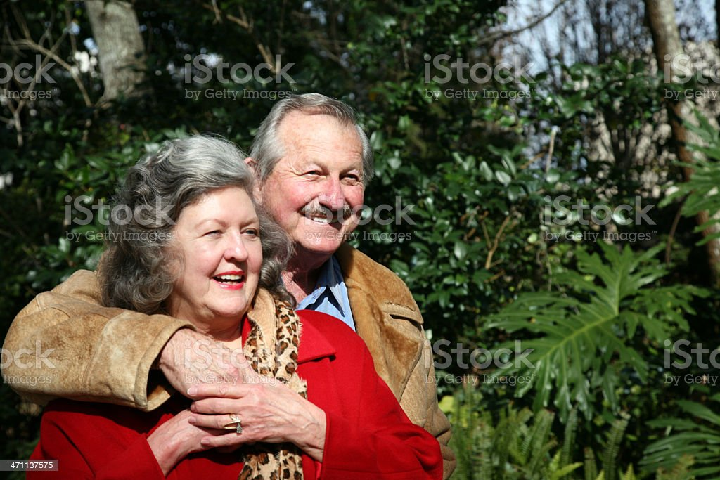 Attractive Happy Active Senior Couple Hugging and Holding Hands Outdoors royalty-free stock photo