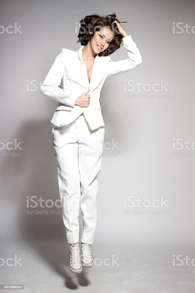 attractive happy dance model jumping in studio wearing white suit stock photo