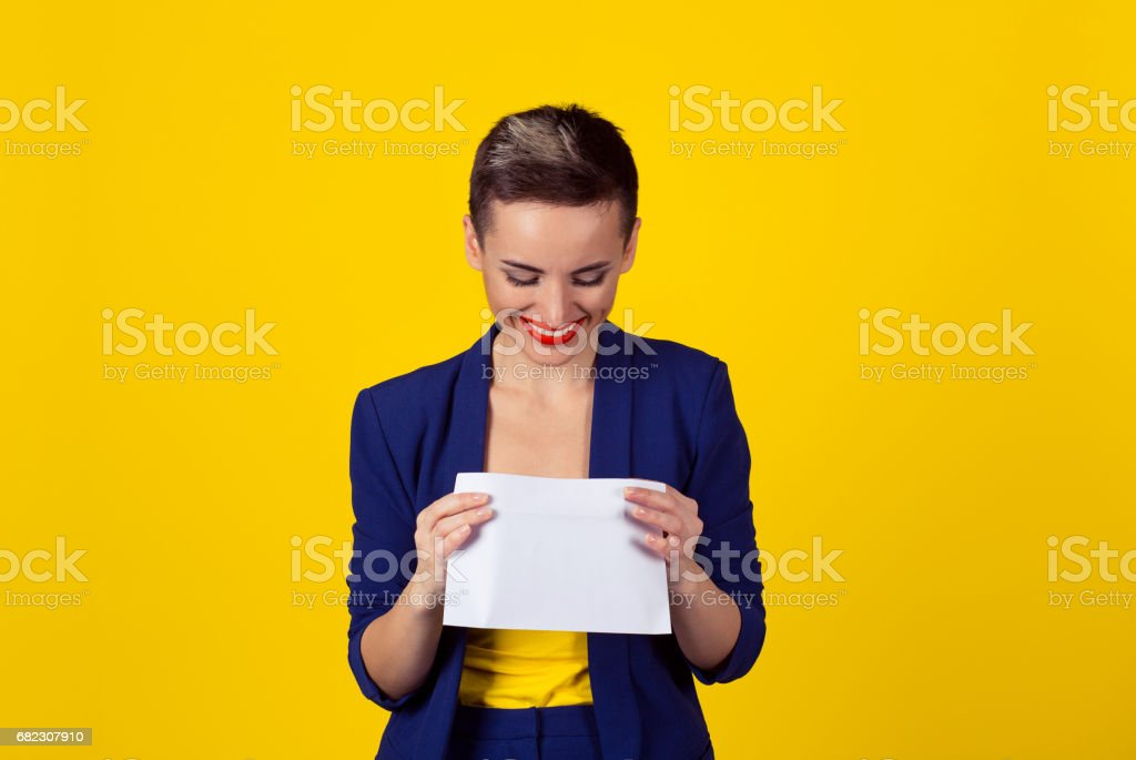 Attractive happy young business woman smiling opening looking inside a white envelope or letter to the camera with a pleased smile isolated yellow background wall with copy space. Fresh mail is here stock photo