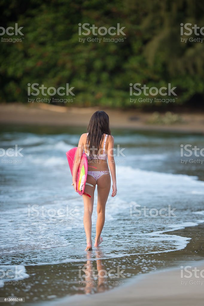 Attractive hawaiian female surfer at the beach stock photo