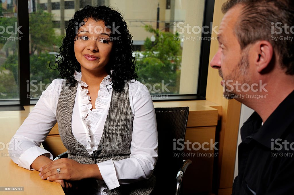 Attractive Hispanic Business Woman Gives Male Coworker Questioning Glance stock photo