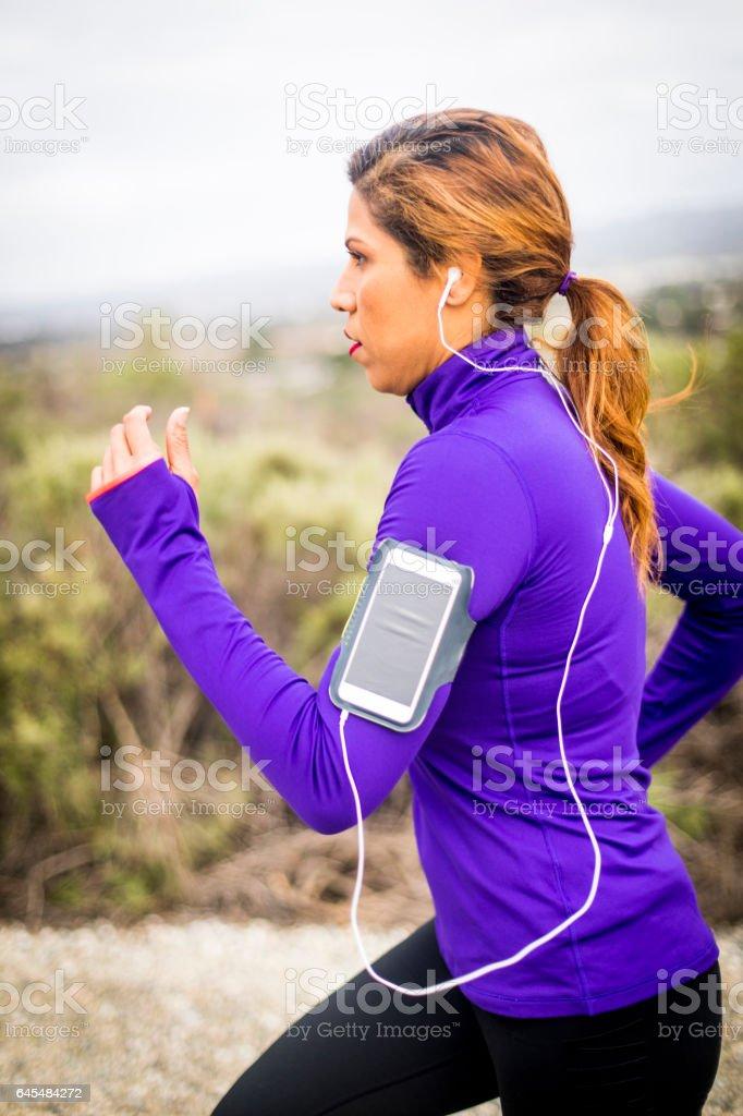 Attractive Hispanic woman running by herself stock photo