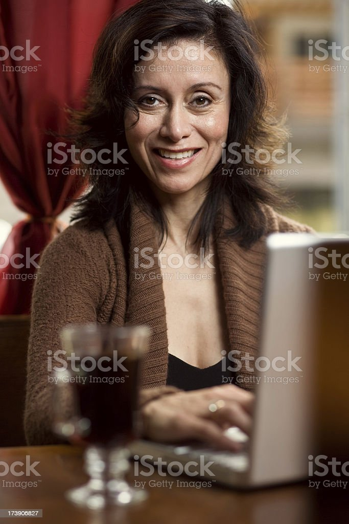 attractive hispanic woman typing on laptop with cup of coffee royalty-free stock photo