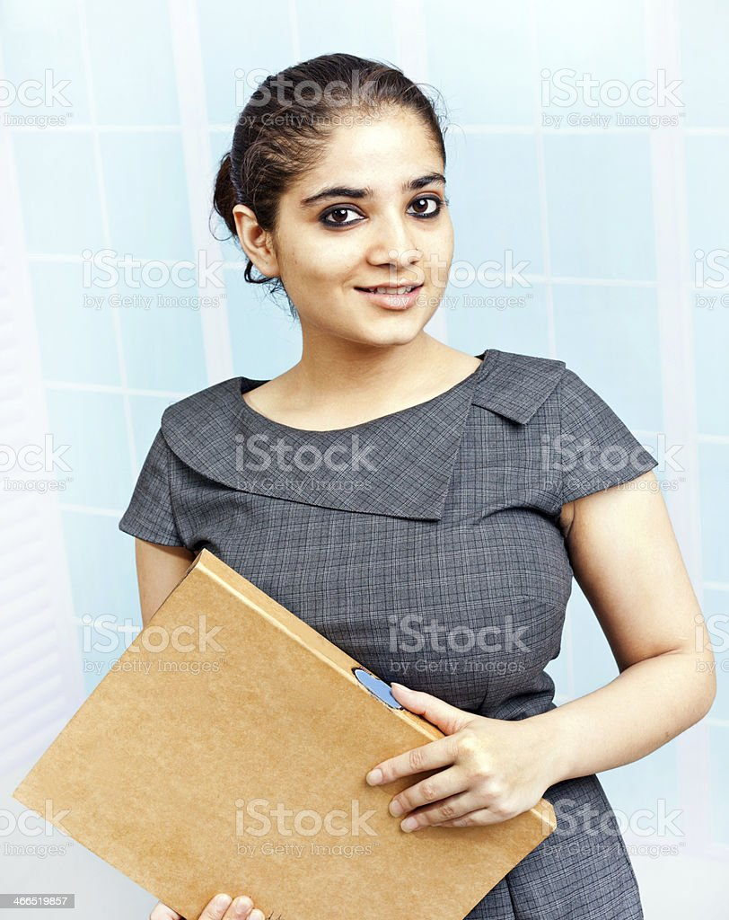 Attractive Indian Businesswoman Office Worker looking at File Document royalty-free stock photo