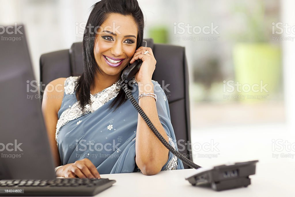 attractive indian receptionist talking on the phone stock photo