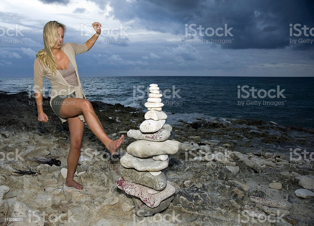 Attractive lady kicking over tower of rocks. royalty-free stock photo