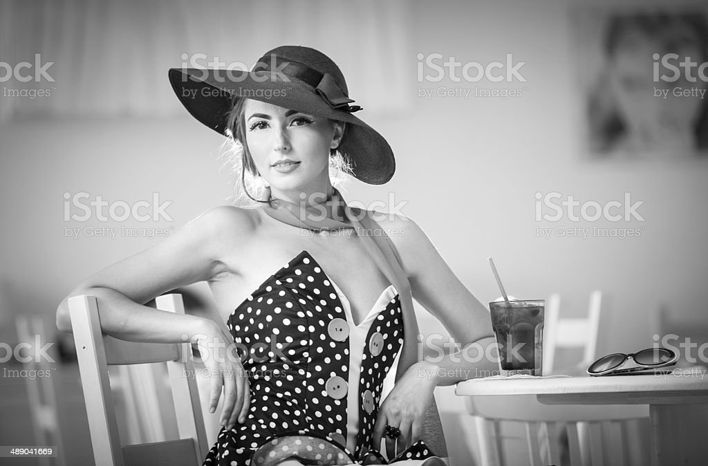 attractive lady with hat and scarf sitting in restaurant stock photo