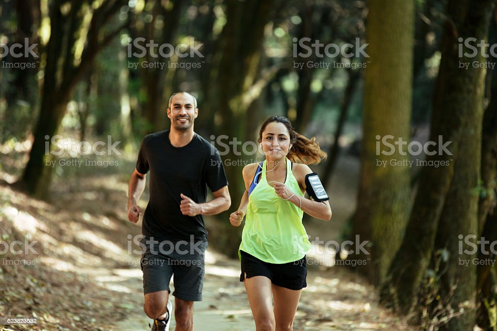 Attractive latin couple running and looking at camera stock photo