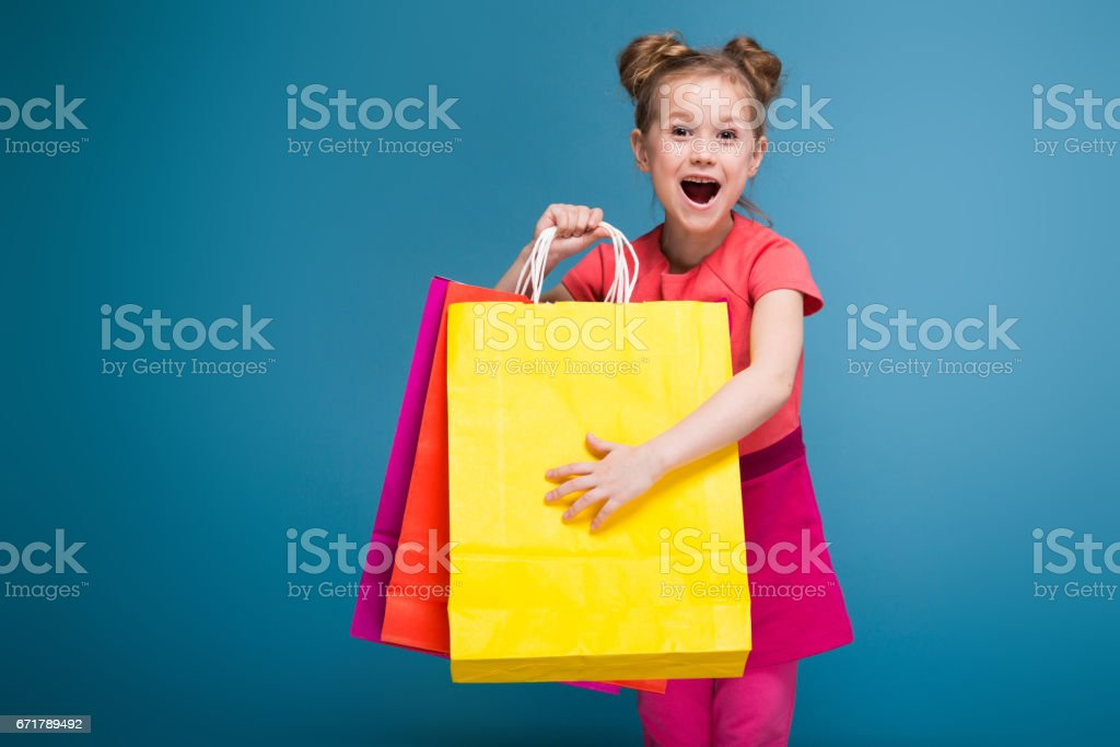 Attractive little cute girl in pink dress holds purple paper bag stock photo