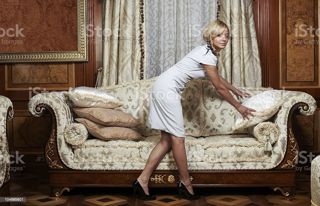 Attractive maid making a sofa in luxury hotel royalty-free stock photo