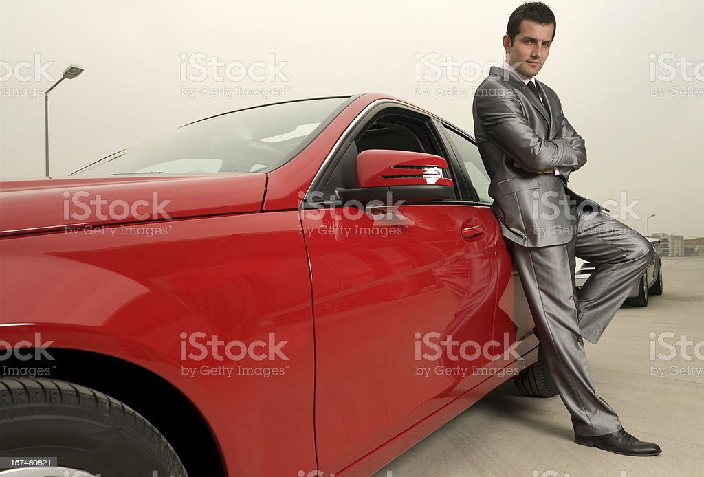 Attractive male and his red sports car royalty-free stock photo