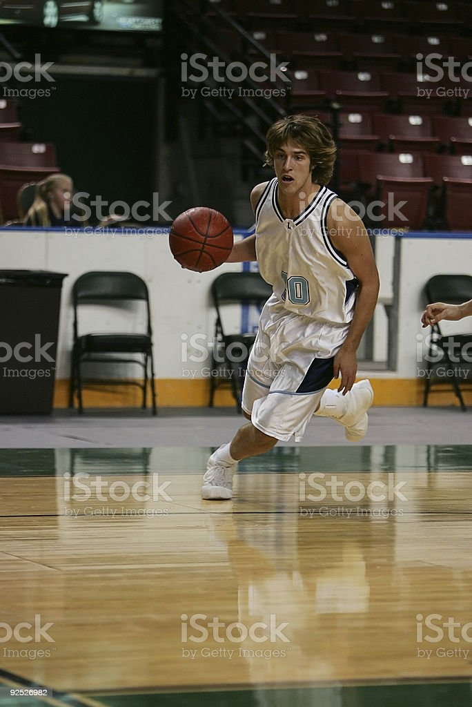 Attractive Male Basketball Player Dribbles Agressively to Baseline stock photo