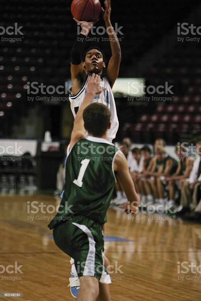 Attractive Male Basketball Player Releases Shot Over Defender royalty-free stock photo