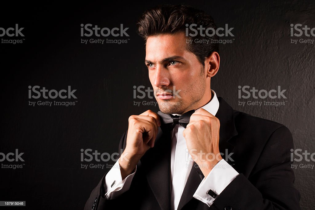 Attractive Male Model Tying Bow Tie stock photo