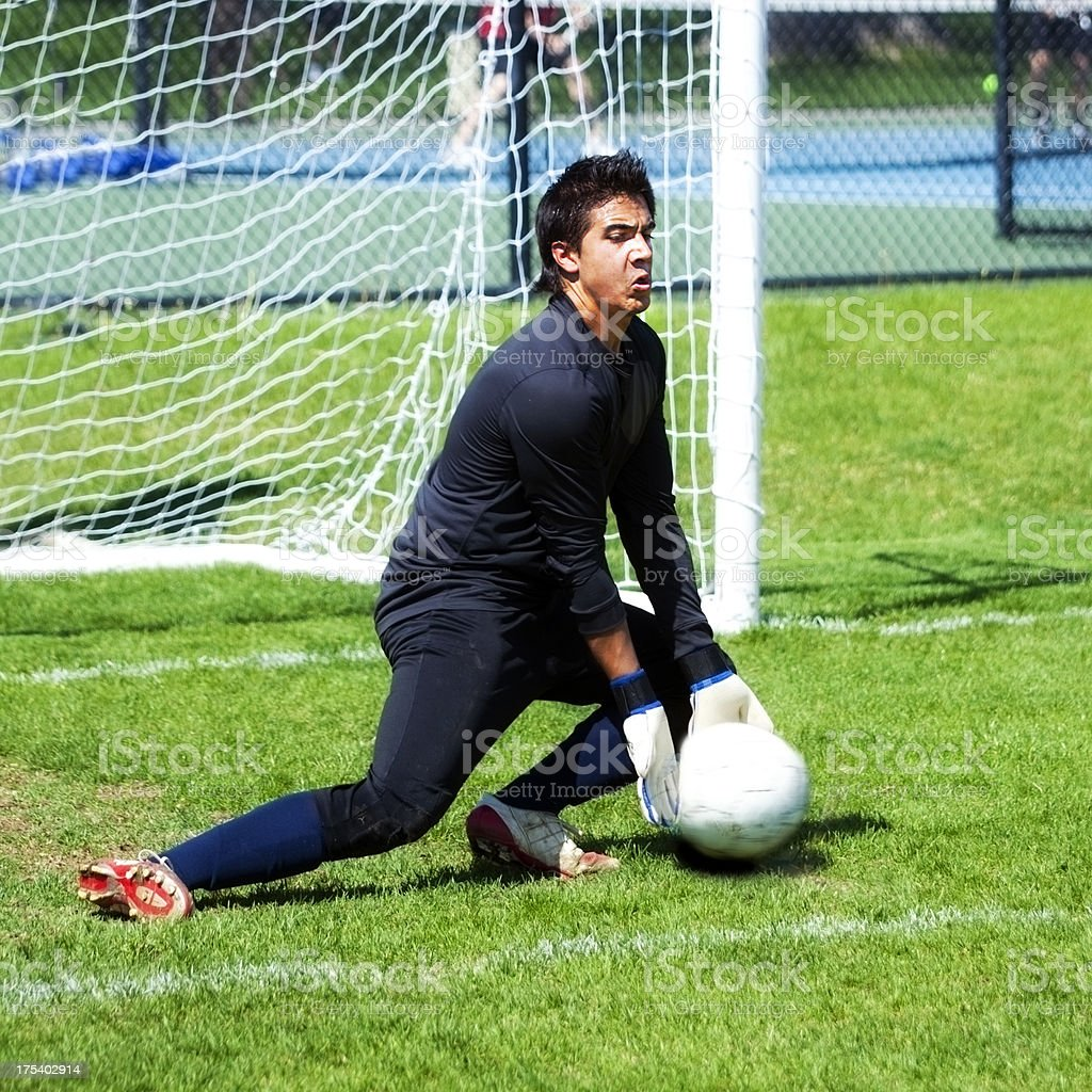 Attractive Male Soccer Goalie Digs Deep to Save Goal Kick royalty-free stock photo