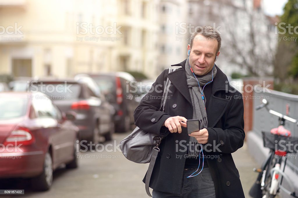 Attractive man checking his mobile in a street stock photo
