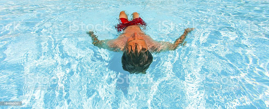 attractive man enjoys swimming in the pool royalty-free stock photo