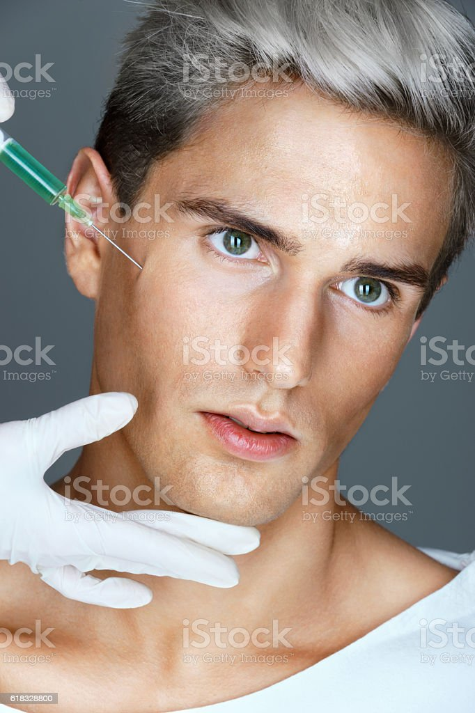 Attractive man getting lifting botox injection stock photo