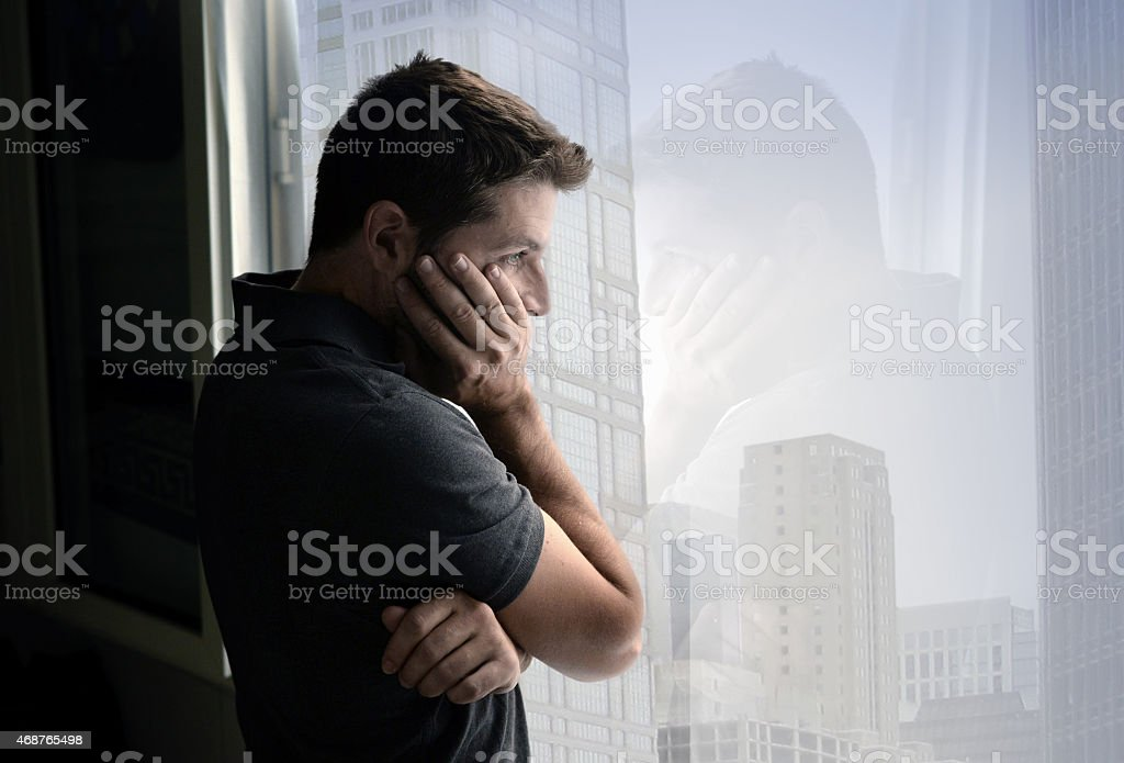 attractive man looking through window suffering emotional crisis and depression stock photo