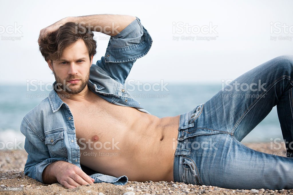 Attractive man on the beach stock photo