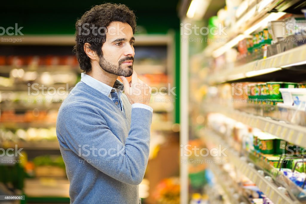 Attractive man shopping in a supermarket stock photo
