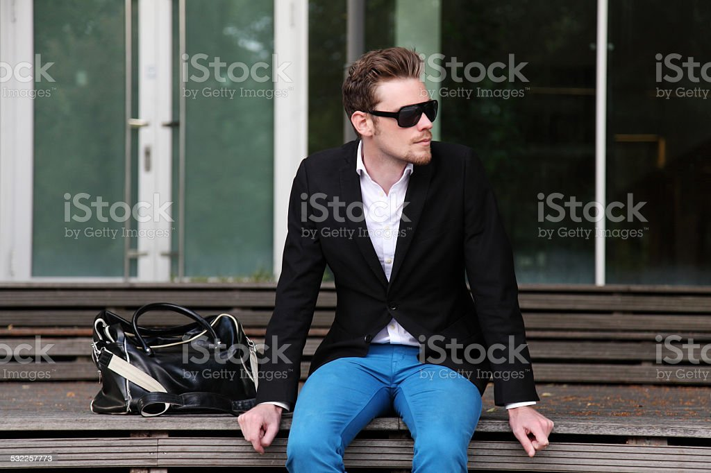 Attractive man sitting on a bench outside stock photo
