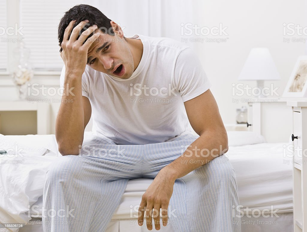 Attractive Man Sitting on His Bed Yawning royalty-free stock photo