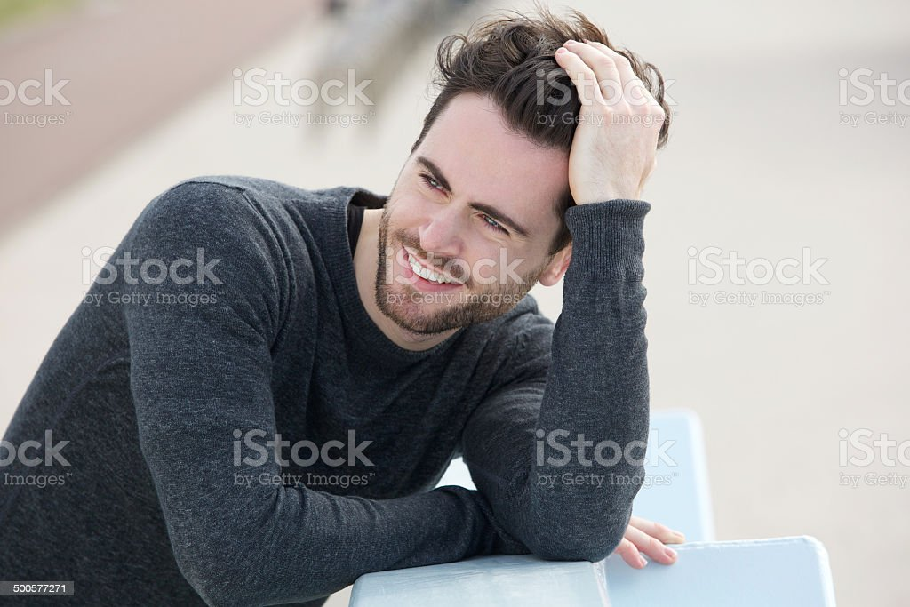 Attractive man smiling with hand in hair stock photo