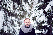 Attractive man standing in snowy coniferous forest
