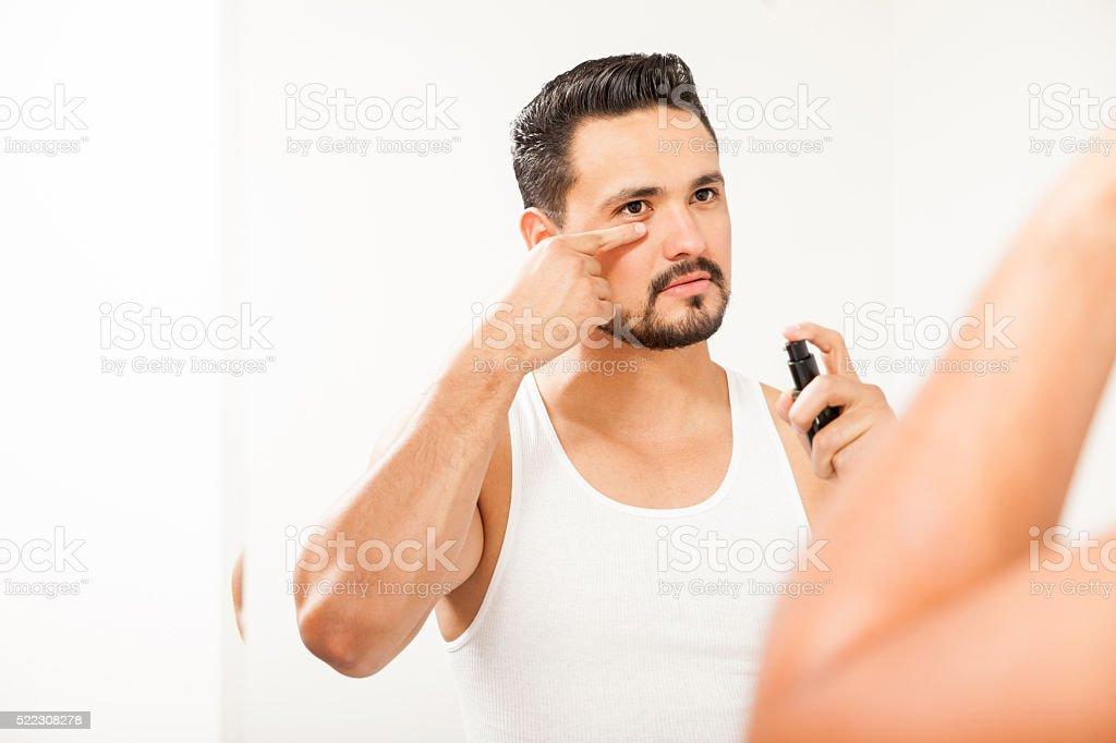 Attractive man using anti-aging cream stock photo