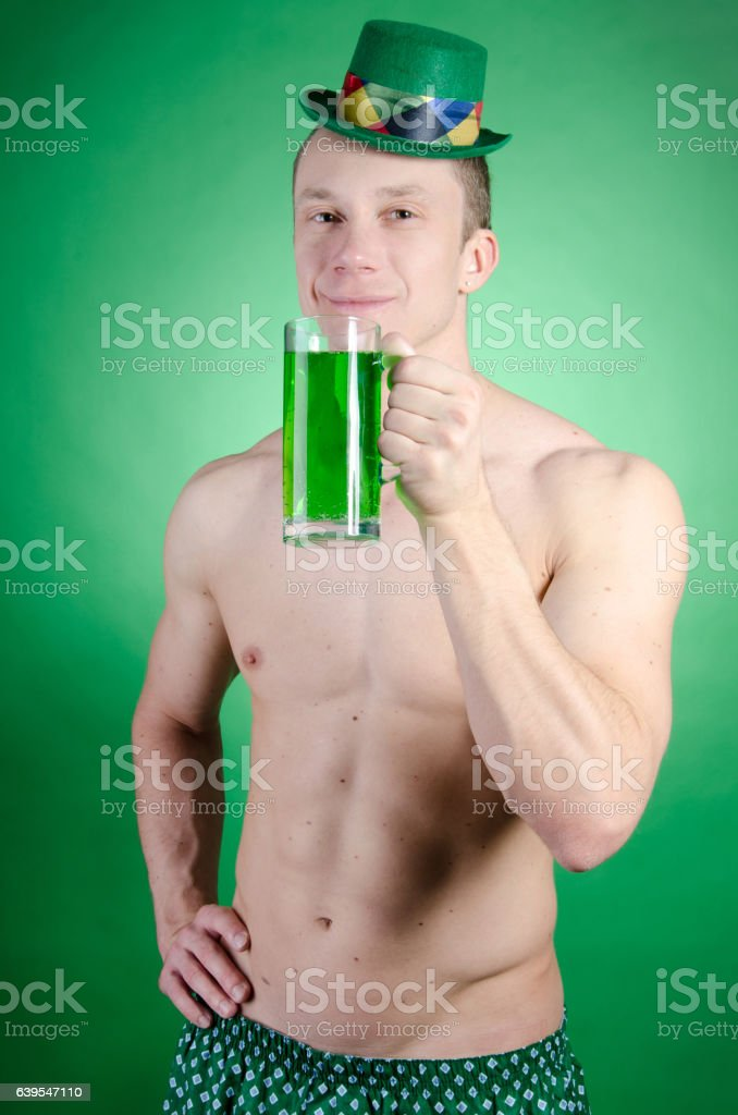 Attractive man with a mug of green drink. stock photo