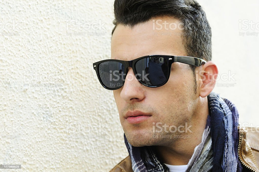 Attractive man with tinted sunglasses in urban background royalty-free stock photo