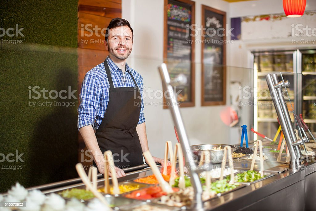 Attractive man working at a salad bar stock photo
