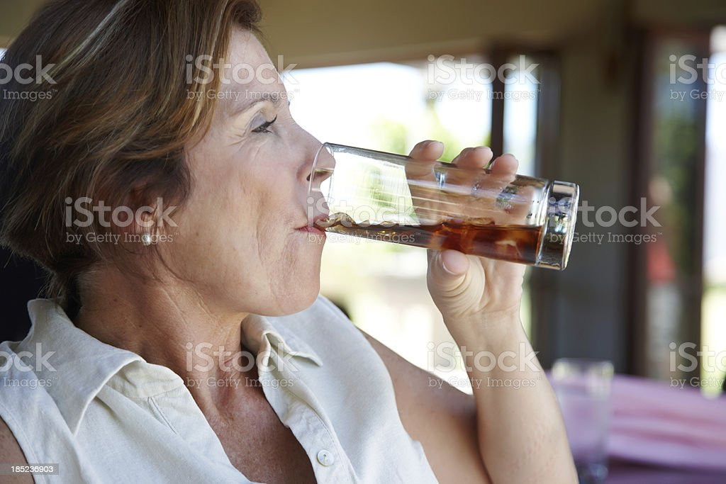 Attractive mature woman drinking soda stock photo