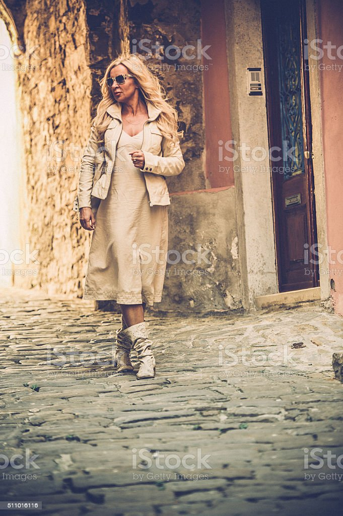 Attractive Mature Woman In casual beige Clothings Walking in Piran, Slovenia stock photo