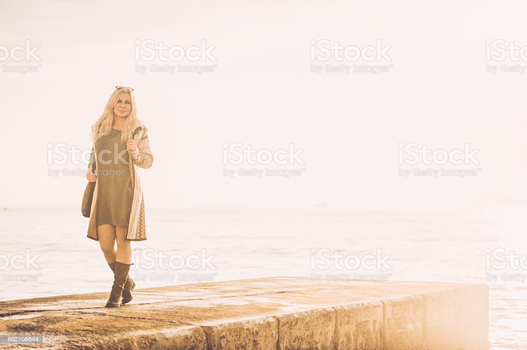 Attractive Mature Woman In Woolen Clothings Walking stock photo