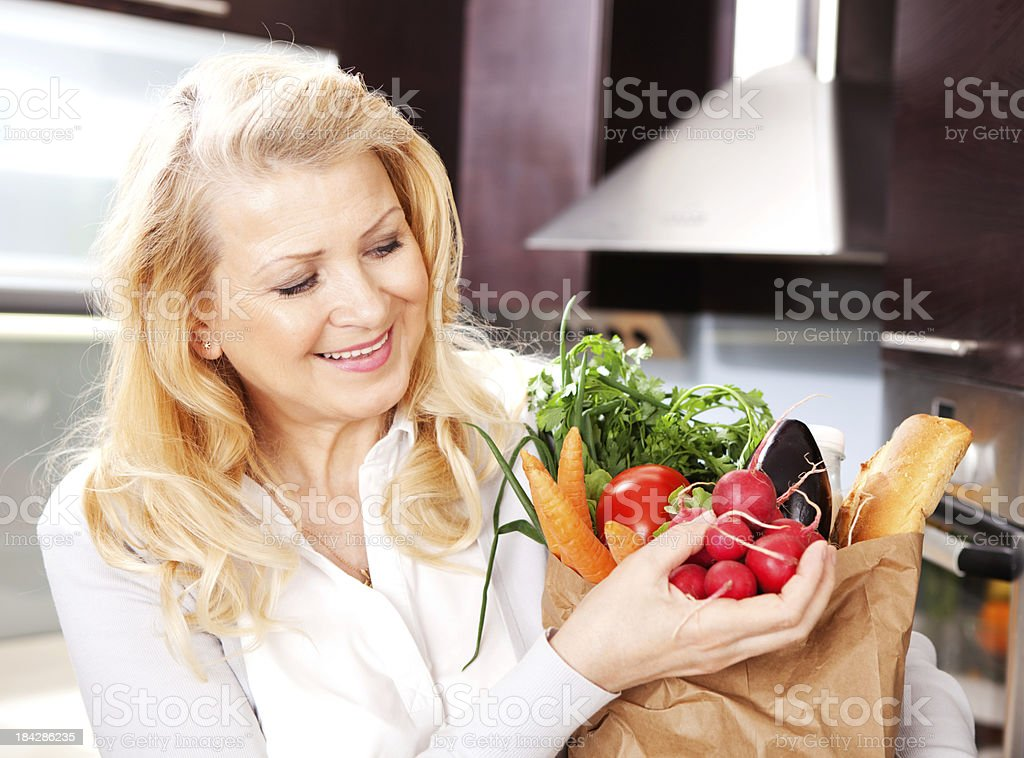 Attractive mature woman with grocery bag. royalty-free stock photo