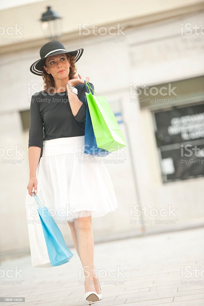 Attractive Mature Woman with Multi Colored Shopping Bags on Street stock photo